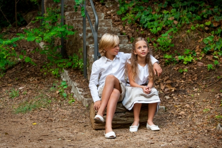 Portrait of cute young couple sitting on log in woods. photo
