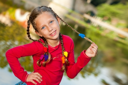 Close up outdoor portrait of cute girl wearing braids. photo