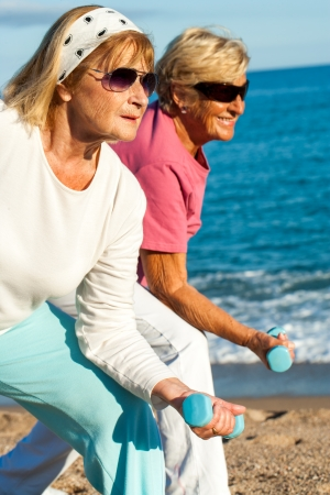 Close up portrait of two golden age women doing early morning workout on beach. photo