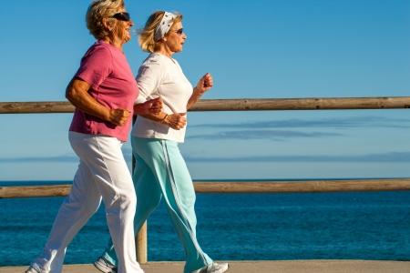 practicing: Action portrait of elderly women jogging together outdoors.