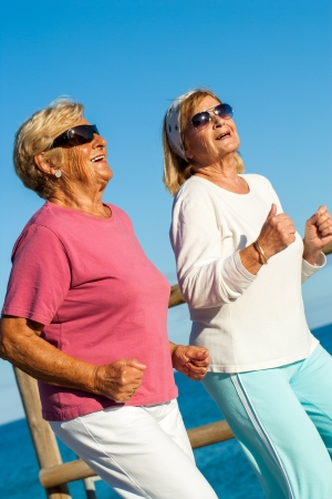 Portrait of happy senior ladies jogging together at seaside. Stock Photo - 23712774