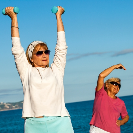 Close up portrait of two senior ladies working out with weights on beach. photo