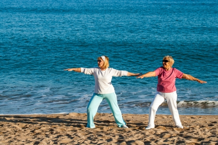 Two senior ladies doing yoga exercises on beach.  photo