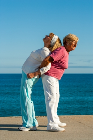 Portrait of two senior ladies helping each other with stretching exercise outdoors. Stock Photo - 23714359
