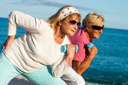 Two elderly fitness girlfriends working out together on beach. Stock Photo
