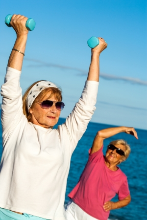 Senior woman doing exercise with weights on beach. photo