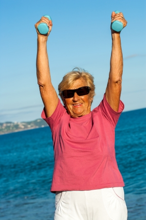 golden ager: Senior woman doing muscle exercise on beach.