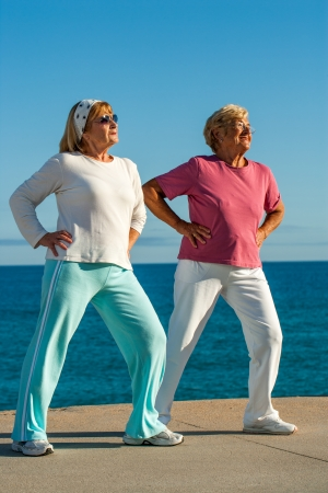 Two senior women doing leg stretching exercise at seafront. photo