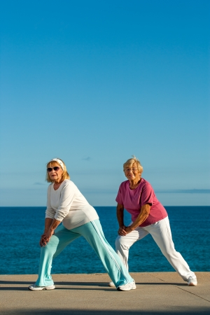 Two golden age women stretching legs at seafront. photo
