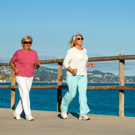 active seniors: Senior fitness women jogging together at beachfront.