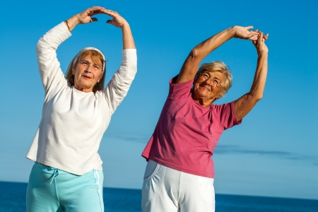 Portrait of two senior fitness ladies stretching arms outdoors.