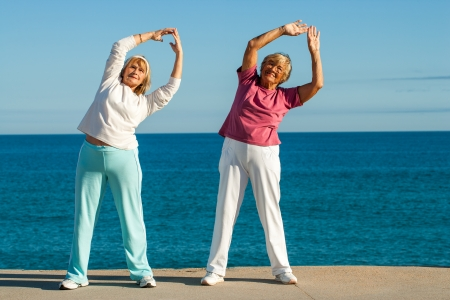 seafront: Portrait of senior fitness ladies stretching arms together at seafront.