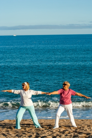 Portrait of two female elderly ladies doing yoga on beach. photo