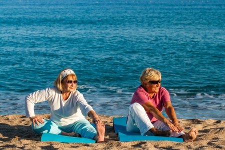 Two golden age women doing health care exercise on beach.  photo