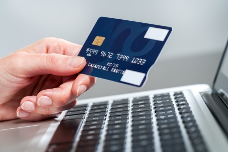 Macro close up of female hand holding credit card on laptop. Stock Photo - 24896624