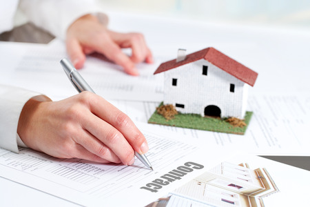 Close up of female hand reviewing real estate contract.
