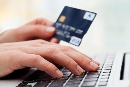 tarjeta de credito: Extreme close up de mano femenina escribiendo o teclado con tarjeta de cr�dito. Foto de archivo