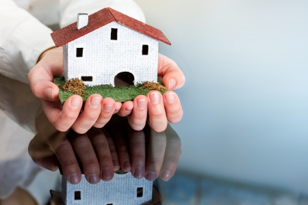 Close up of female hands holding small wooden house. photo