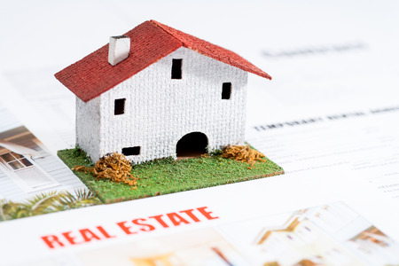 Close up of small toy house on real estate documents. photo