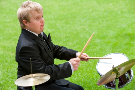 Portrait of handicapped drummer in suit playing outdoors.