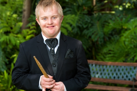 Portrait of handicapped drummer boy in black suit outdoors.