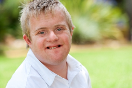 down syndrome: Close up facial portrait of handicapped young man outdoors.