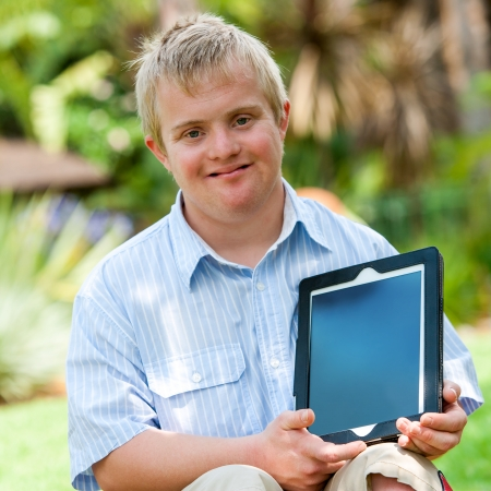 Down Syndrome: Close up portrait of disabled boy holding blank tablet with copy space outdoors. Stock Photo