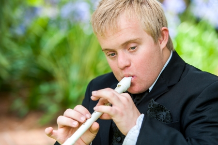 Close up portrait of disabled young man playing block flute outdoors.