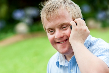 syndrome: Close up portrait of handicapped boy talking on smart phone outdoors.
