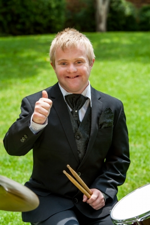 disadvantaged: Portrait of young disabled musician with thumbs up outdoors.