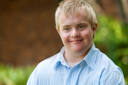 physically: Close up portrait of young disabled man outdoors.