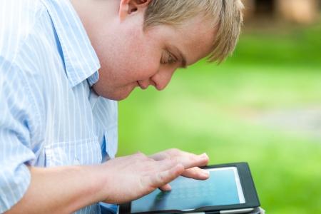 personas discapacitadas: Cerrar un retrato de un niño con discapacidad al aire libre con la tableta digital. Foto de archivo