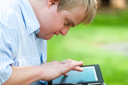 syndrome: Close up portrait of handicapped boy outdoors with digital tablet.