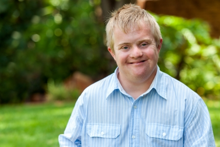 Down Syndrome: Portrait of handsome handicapped boy in blue shirt outdoors. Stock Photo