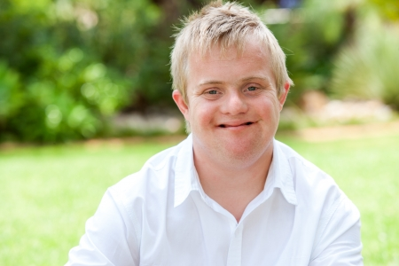 handicapped person: Close up portrait of boy with down syndrome in white shirt outdoors. Stock Photo