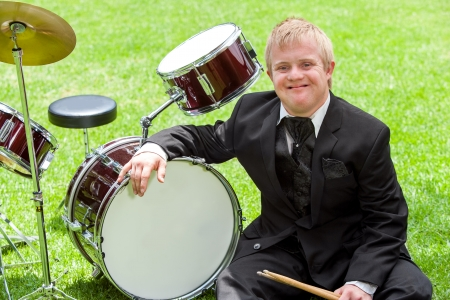 Portrait of young disabled musician next to drums outdoors.