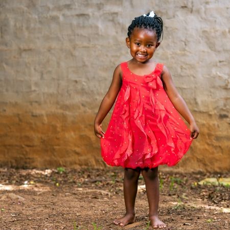 africa american: Full length portrait of cute african girl showing red dress outdoors.