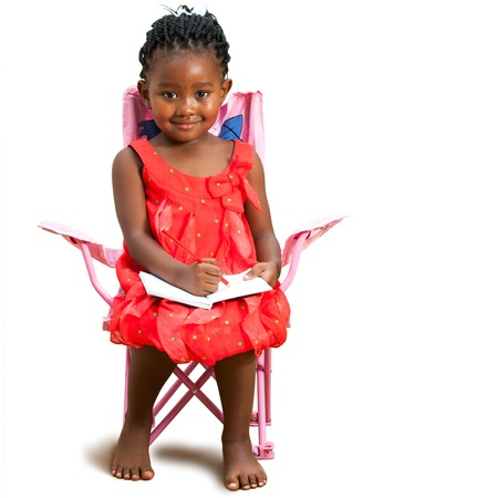 Full length portrait of little african girl sitting with note book.Isolated on white background.