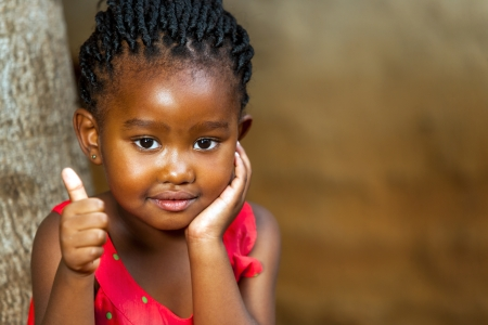 contentedness: Close up facial portrait of african girl doing thumbs up outdoors. Stock Photo