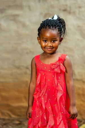 africa child: Close up portrait of cute african girl standing in red dress outdoors.