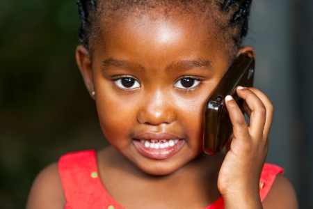 red cells: Extreme facial portrait of cute african girl having conversation on smart phone. Stock Photo
