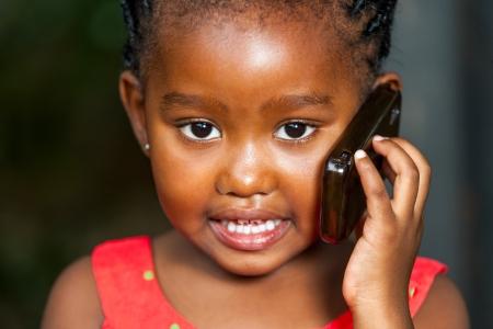 Retrato facial extrema de la muchacha linda africano que tiene una conversación en el teléfono inteligente.