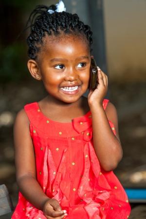 Close up Portrait von niedlichen afrikanisches Mädchen mit Gespräch zu Smartphone im Freien.