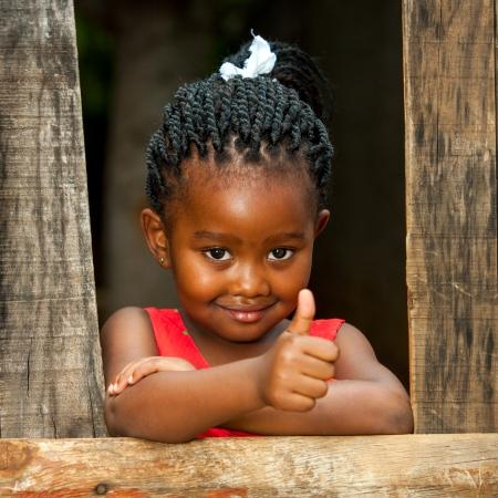 Retrato de la pequeña niña africana que hace los pulgares para arriba en la cerca de madera. Foto de archivo