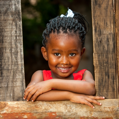 baby hairstyle: Close up portrait of pretty african youngster leaning on wooden fence outdoors.