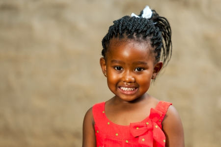 ethnic children: Close up portrait of little african girl with braided hair outdoors.