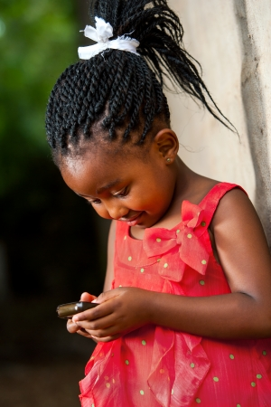 Close up portrait of cute african girl with braided hair playing on smart phone. photo