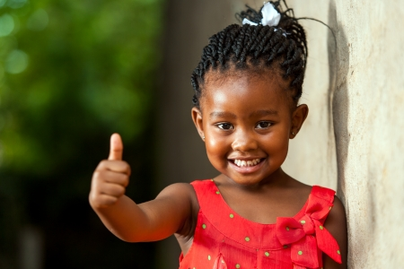 sorrisos: Retrato de pequeno feliz Menina africana que faz os polegares acima do sinal ao ar livre.