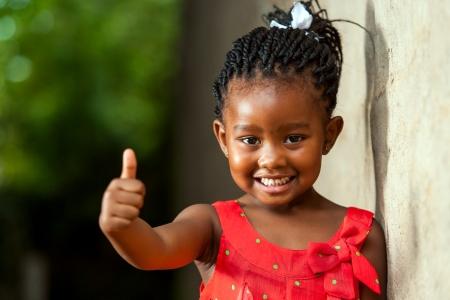 Retrato de poco feliz niña africana que hace los pulgares para arriba signo al aire libre.