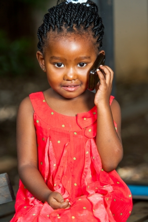 Close up portrait of cute african girl talking on cell phone outdoors. photo